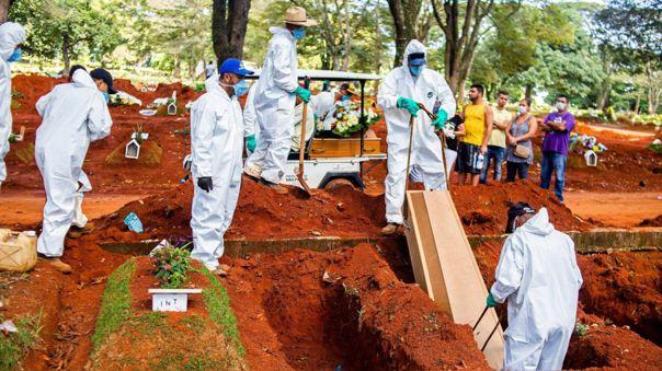Empleados de una funeraria entierran a una víctima de la COVID-19 en el cementeario Vila Formosa.
